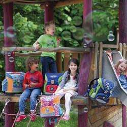 Kinder und die vier DerDieDas Schulranzen auf dem Spielplatz.