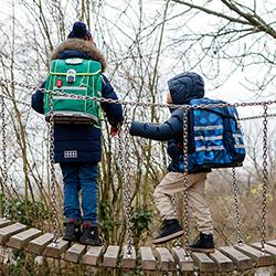 Zwei Mädchen mit McNeill Ranzen klettern auf dem Pausenhof.